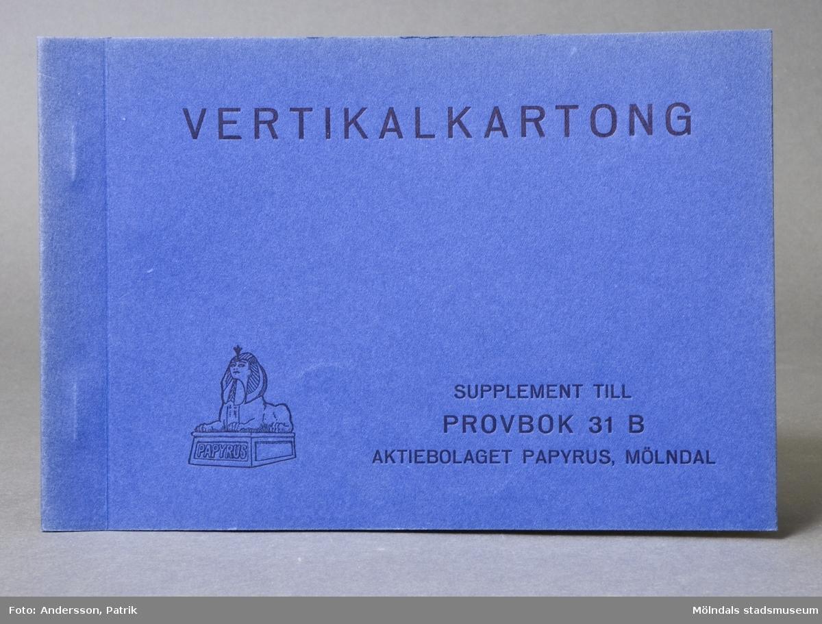 """Häfte med prover, """"Vertikalkartong"""". Pärm av blå kartong med svart tryck, """"Supplement till Provbok 31B"""". Papyrus logotyp med sfinx på fundament och tillverkarnamn. 3 st provark med produktinformation i färgerna vit, gul och brun. Litteratur: Papyrus 1895-1945, Minnesskrifter, Esseltes Göteborgsindustrier AB, Göteborg 1945."""