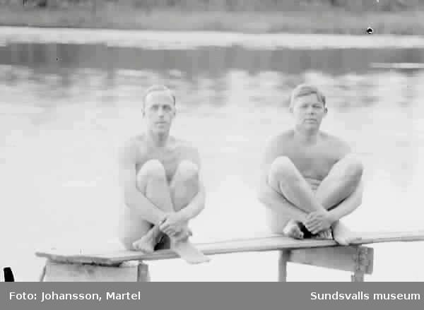 Två nakna män sitter på brygga.