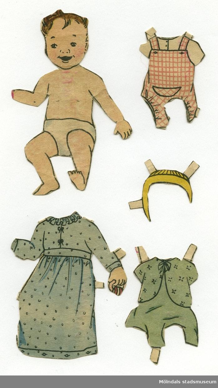 """Pappersdocka med kläder, urklippt ur tidning på 1950-talet. Docka och kläder är märkta """"Ann-Mari"""" på baksidan - dockans namn. Dockan föreställer ett spädbarn med brunt hår, iklädd blöja/underbyxa. Ena handen saknas. Garderoben består av två lek- och sparkdräkter, samt en nattsärk. Docka och kläder förvaras i ett brunt C6-kuvert, märkt """"Ann-Mari"""" och """"Lennart"""" (MM 04665), som också förvaras däri. Kuvertet har ursprungligen kommit från Göteborgs stads Fastighetskontor."""