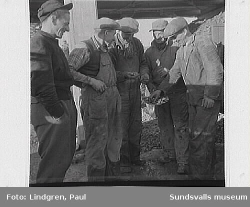 Rännö by, Matfors. Män arbetar med sten, pojkar spelar kula, fabrikbyggnad, hus exteriör.