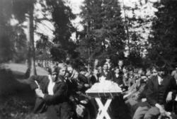 Pojkar sittande kring kaffebord i en park. Skolresa till Tro