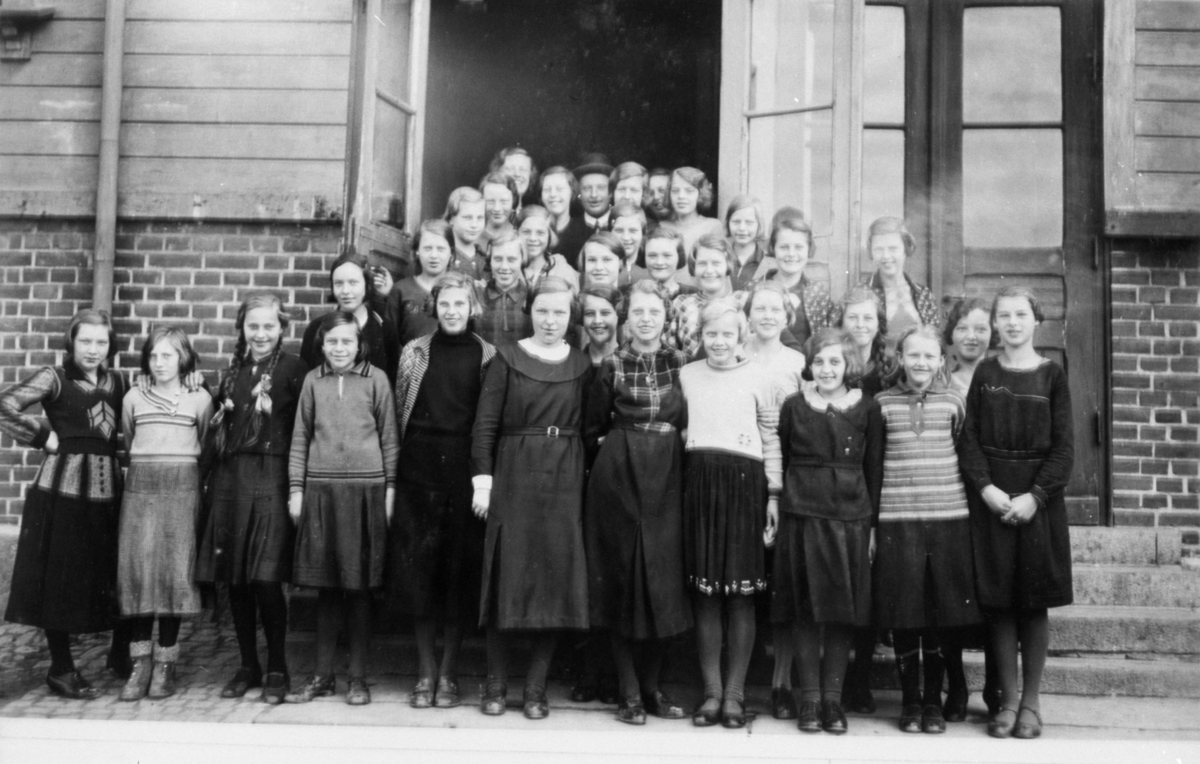 Flickor i 7:e klassen, stående framför Trädgårdsskolans (Kommunala mellanskolans) port.Längst bak står lärarinnan fröken Thorsson och överlärare Ernst Lindstrand.