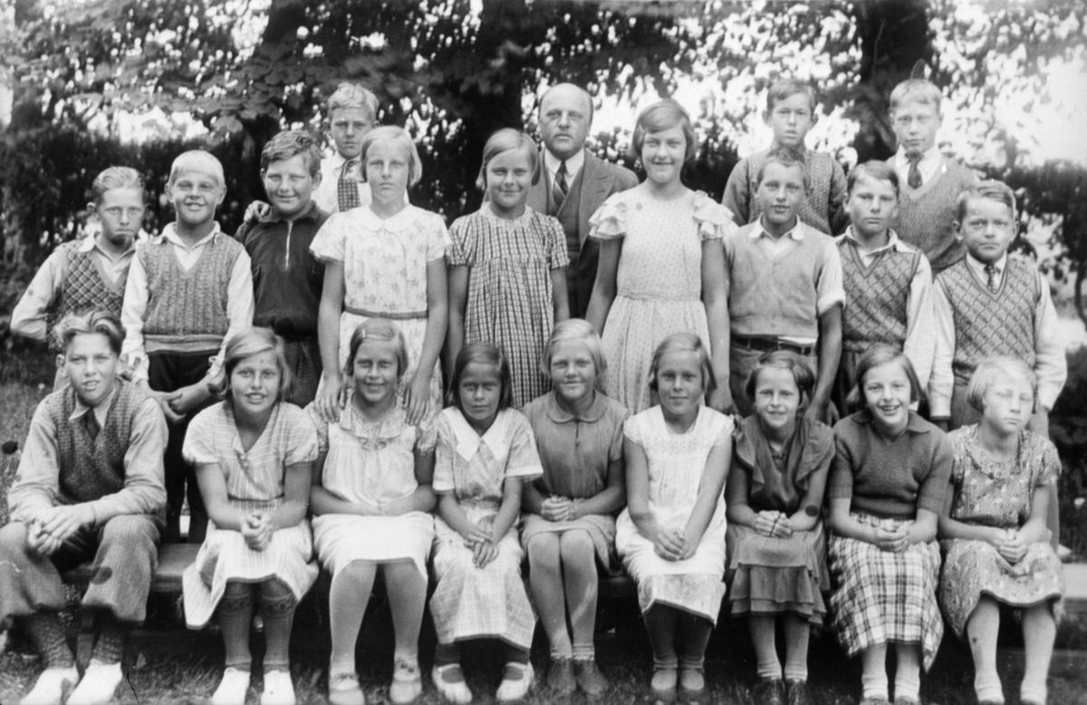 Gruppfoto med flickor och pojkar utomhus, vid Gamla Fässbergsskolan. Magister Daniel Nilsson med elever i 5:e klass. Fässbergsskolan låg i sydvästra Solängen och var en av Mölndals tre äldsta skolor, byggd i början av 1860-talet. Byggnaden brändes ned 1971.