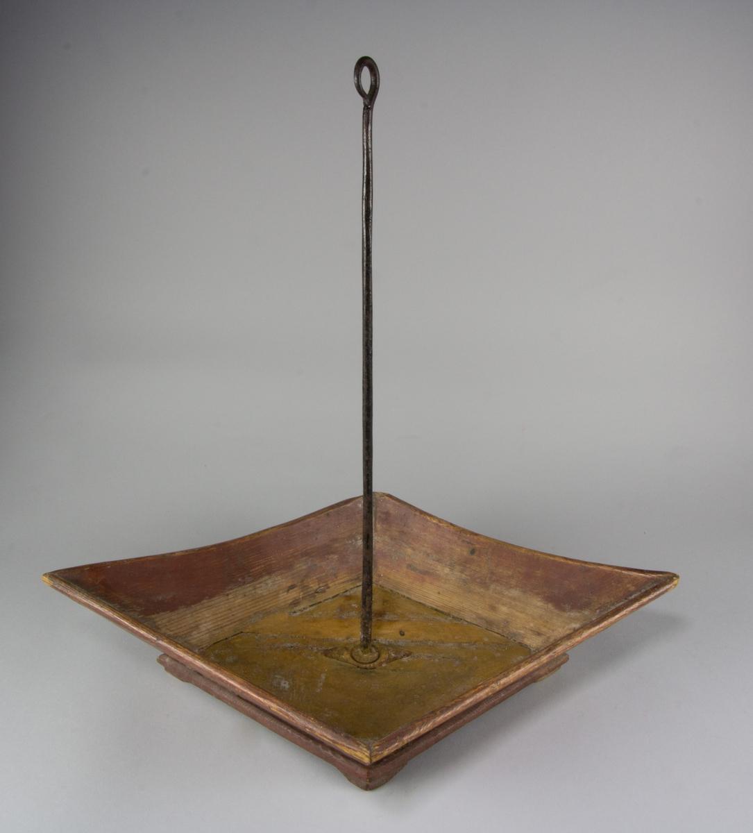 Spottlåda, eller spottkopp, av trä målat i rödbrunt med skaft av järn med märla. Rombformad modell med uppåtpekande hörn. Sidorna fogade mot botten en bit in, så att bottenskivan fungerar som dekorativ list. På fötter av trä.