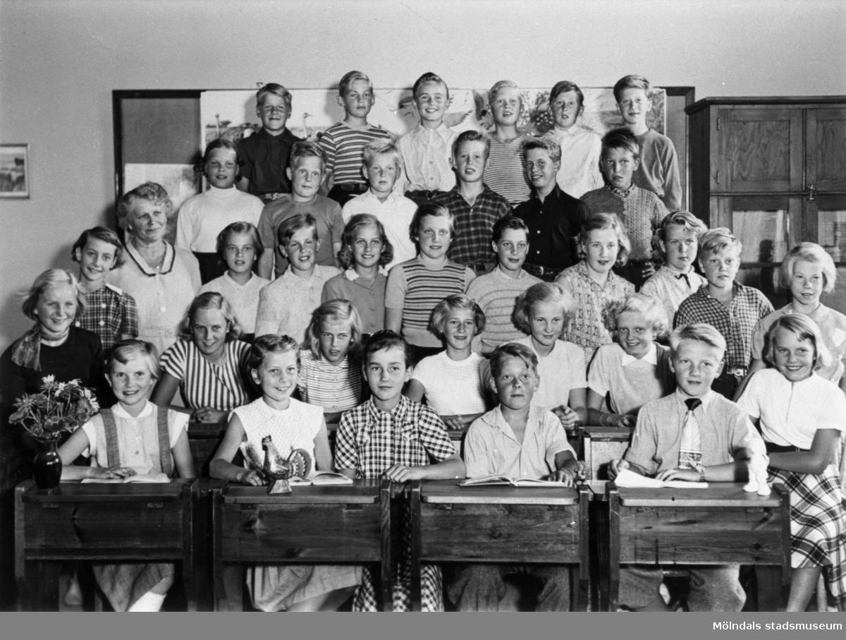 Flickor och pojkar stående i klassrum på Kvarnbyskolan i Mölndal år 1952. De två främsta raderna sitter i bänkar. Med på fotot är givaren Margit Hellström (f. Willumsen).