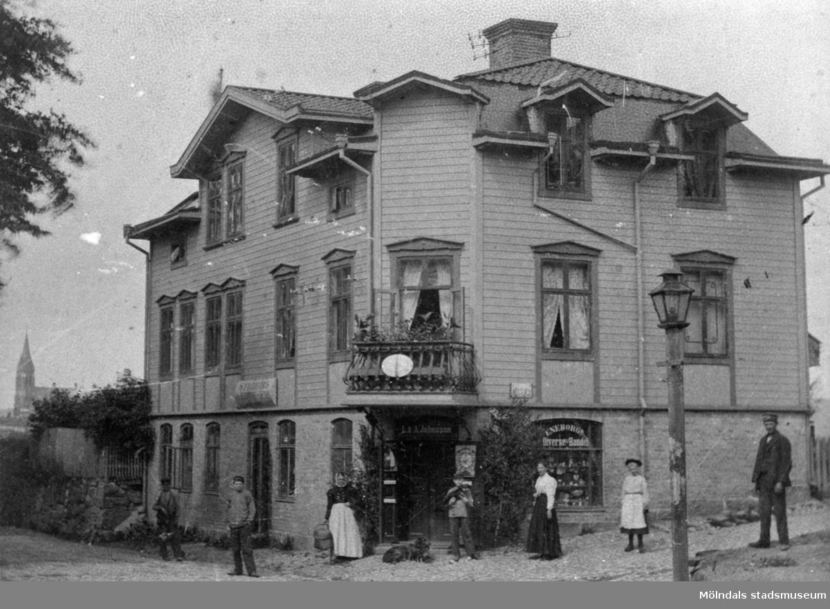"""Kvarnbygatan 23 i Mölndal. Byggnaden rymmer bl a Eneborgs diversehandel. Framför affärens dörr ligger hunden Roy.  Till höger om dörren står """"moster"""" Lovisa Johnsson. Längst till höger John Johansson, privatchaufför hos Papyrus disponent. I våningen med balkong bodde fru Tisell som hade telegraf-och telefonstation i huset."""