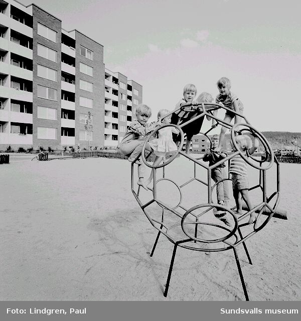 Barn på lekplats, kv Vetet 5, Nacksta. I bakgrunden bebyggelsen vid Nackstavägen 25.