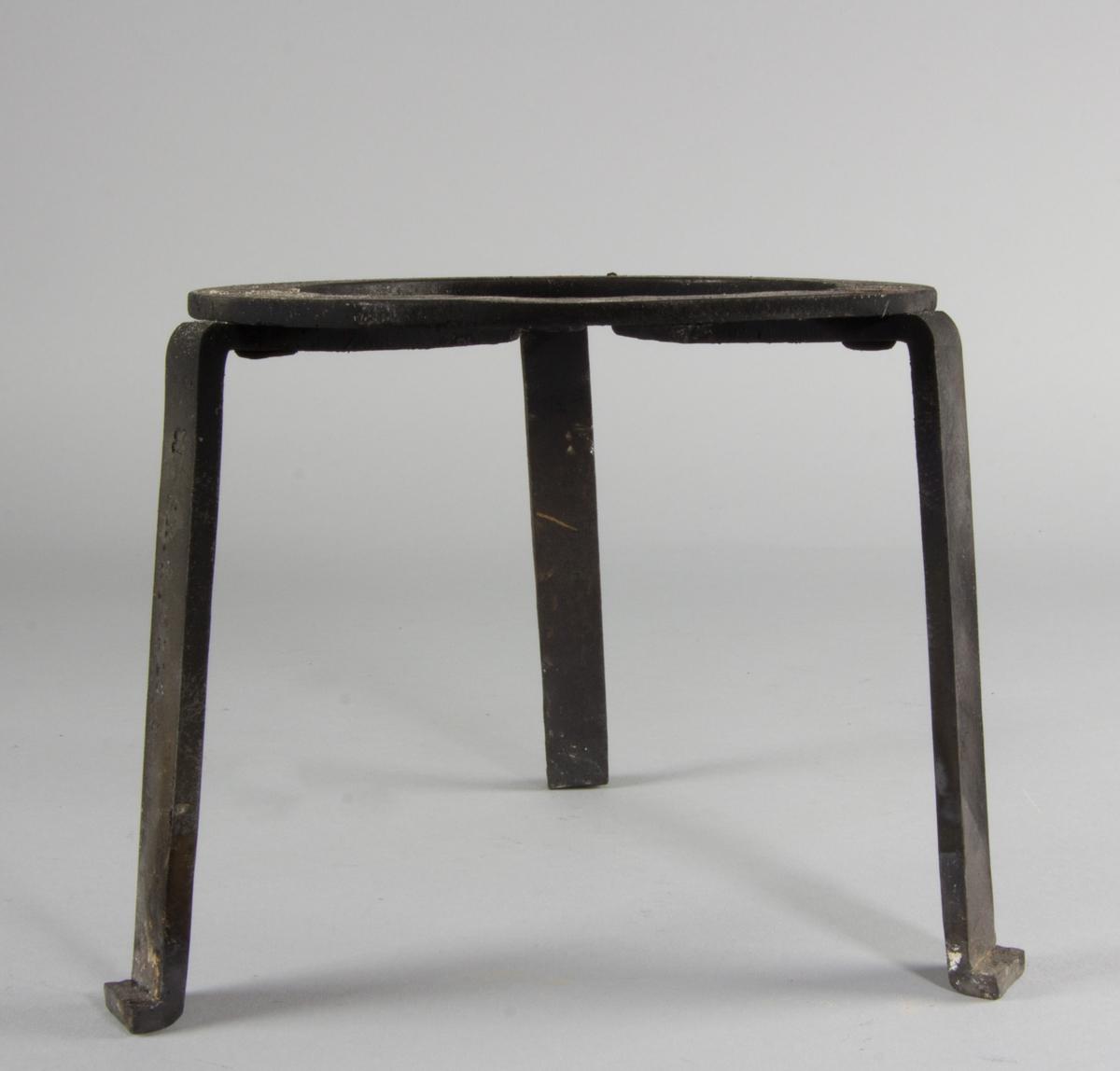 Trefot, smidd av järn. Med tre bockade ben av järn nitade mot en platt ring av järn.