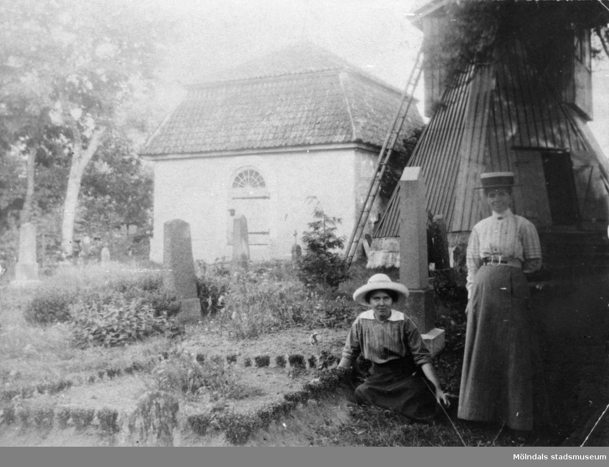 """Valdeborg Johansson (sittande) och Josefina Eriksson på Kållereds kyrkogård, 1910. De sitter och står vid gårdsgraven till Vommedal Östergård, """"Olas"""". Josefina var Valdeborgs moster."""