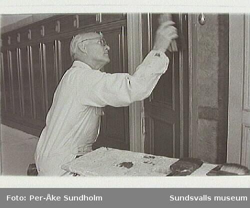 Hantverkföreningens festsal.Målarmästare i arbete med ådring av väggpanel.