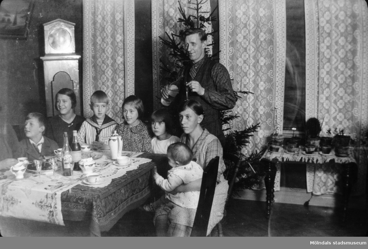 Julafton hemma hos familjen Viktor och Alma Karlsson på Kvarnfallet 31 med släkt. Tidigt 1930-tal. Från vänster: Alf och Rut Zakrisson, syskonen Ivar, Astrid och Margit, modern Alma med Rolf i famnen. Fadern Viktor (morfar till givaren) står upp.