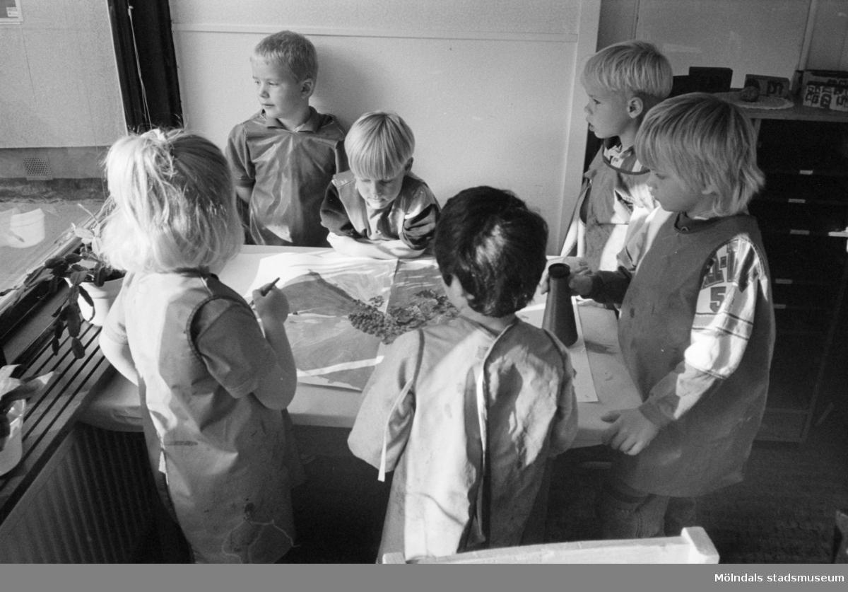 Sex barn står runt ett bord och målar en stor teckning tillsammans. Hoppetossan, Katrinebergs daghem, 1992-93.