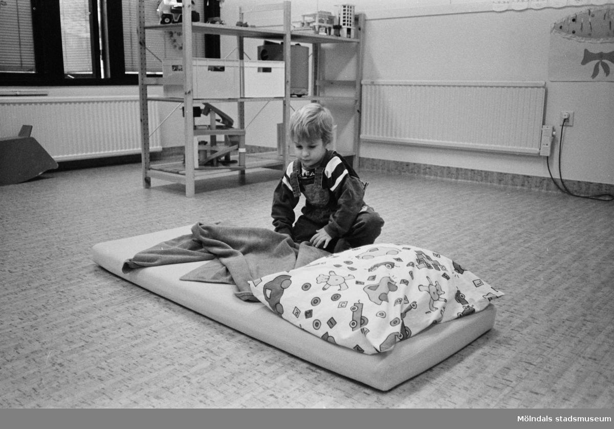 Henrik rättar till filten efter att ha bäddat klart den mjuka madrassen med kudde. Madrassen ligger på golvet i ett lekrum. Lunkentussen, Katrinebergs daghem 1992.