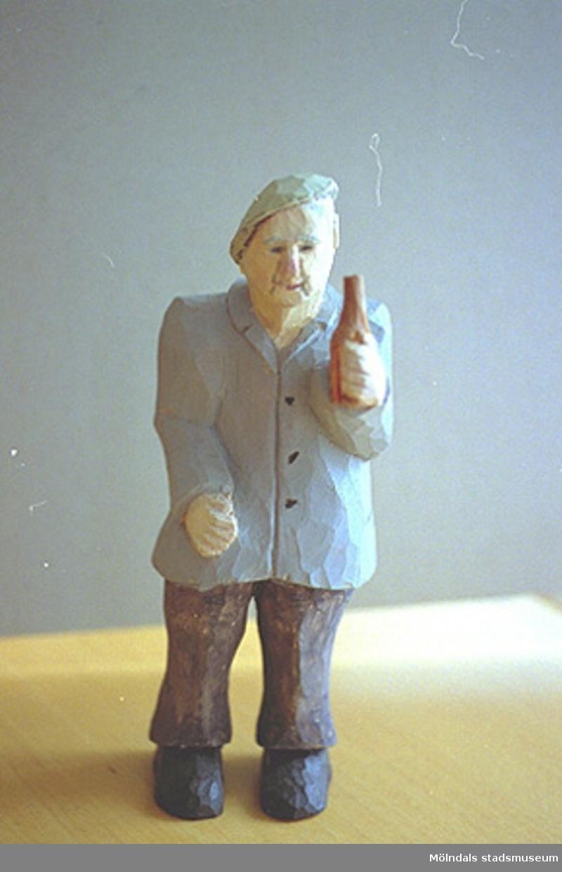 """En gubbe med baskern på sned, håller en flaska i ena handen. Harry Bergmans """"gubbar"""" (träfigurer)."""
