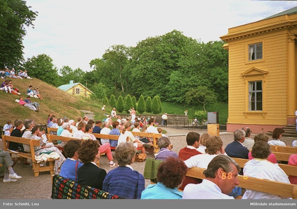 Människor sitter på bänkar och på gräsmattan framför slottet och tittar på ett körframträdande.
