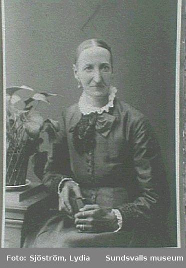 Porträtt av kvinna med krukväxt.
