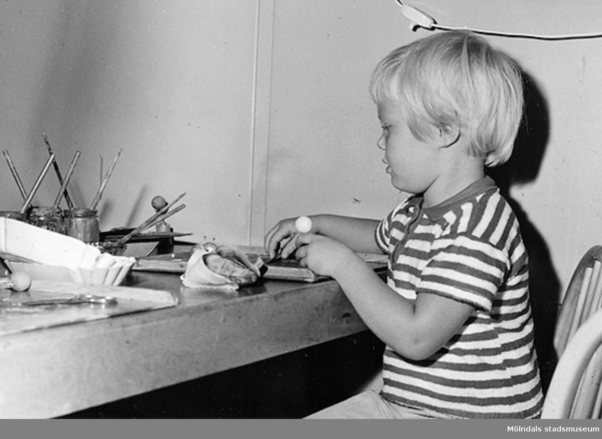 Ett barn målar vid ett bord. Holtermanska daghemmet 1953.