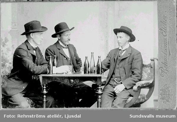 Ateljéfoto. Män med ölflaskor.