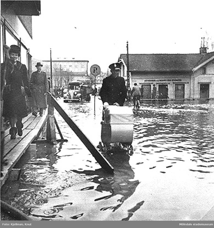 Polisman skjuter barnvagn på Frölundagatan under översvämning, 1940-tal. Från vänster ses gaveln på Frölundagatan 2, Kvarnbygatan 1 (höghuset i bakgrunden) och Kungsbackavägen 1.