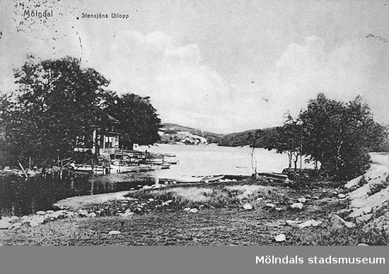 """""""Stensjöns Utlopp"""" (Mölndalsåns utlopp ur Stensjön) sett från södra stranden av utloppet mot Gunnebobro i nordost, cirka 1930. Till vänster ses Sjövillans brygghus och garage."""