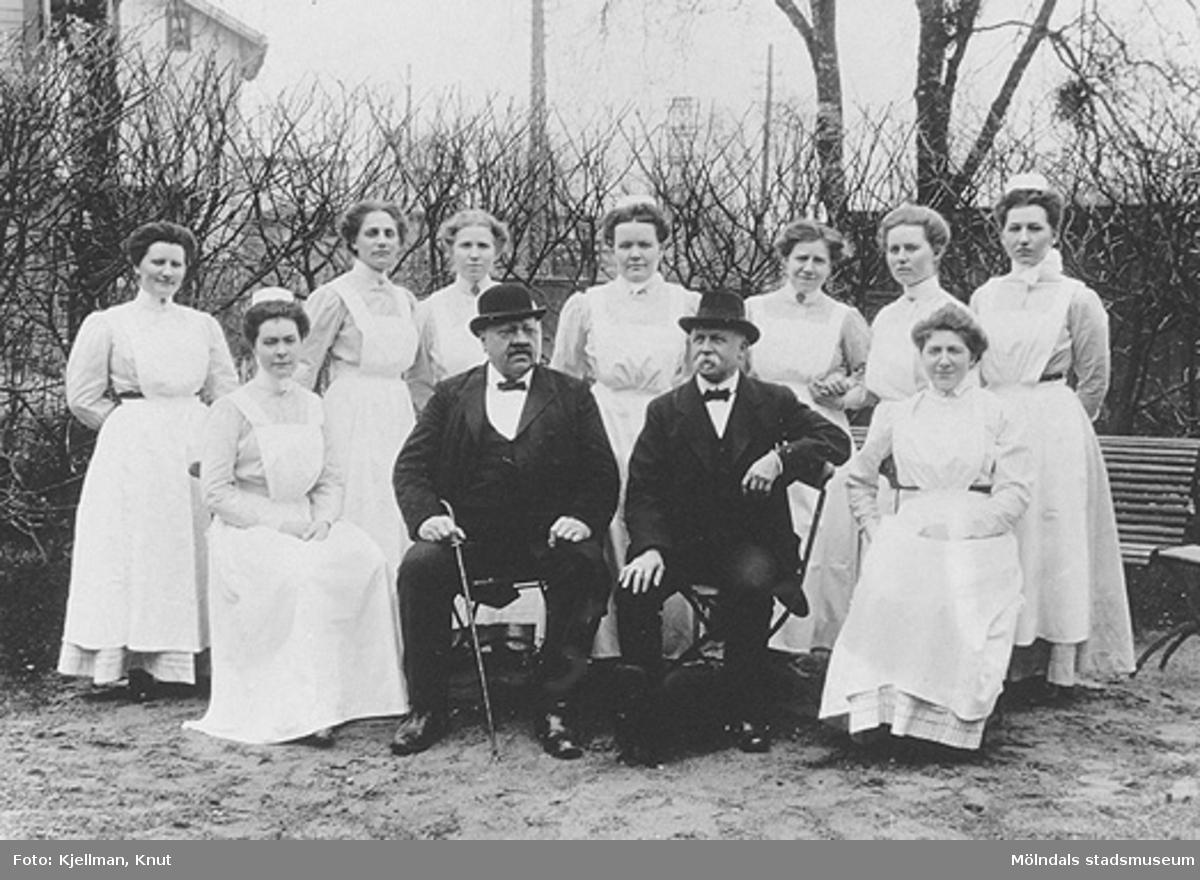 """Under bilden står: """"Minne af Mölndals Sjukstugas 25-årsjubileum den 30 april 1911"""". Man ser doktor Knut Belfrage, sysslomannen och sjuksköterskorna. Dessutom står de uppradade personernas namn och i förekommande fall även titlar, uppräknade. På baksidan av kartongen står: """"Mölndals sjukhus den 30 april 1911, vid dess 25-årsjubileum"""". Kortet finns också registrerat på bild nr. MMF 92:110."""