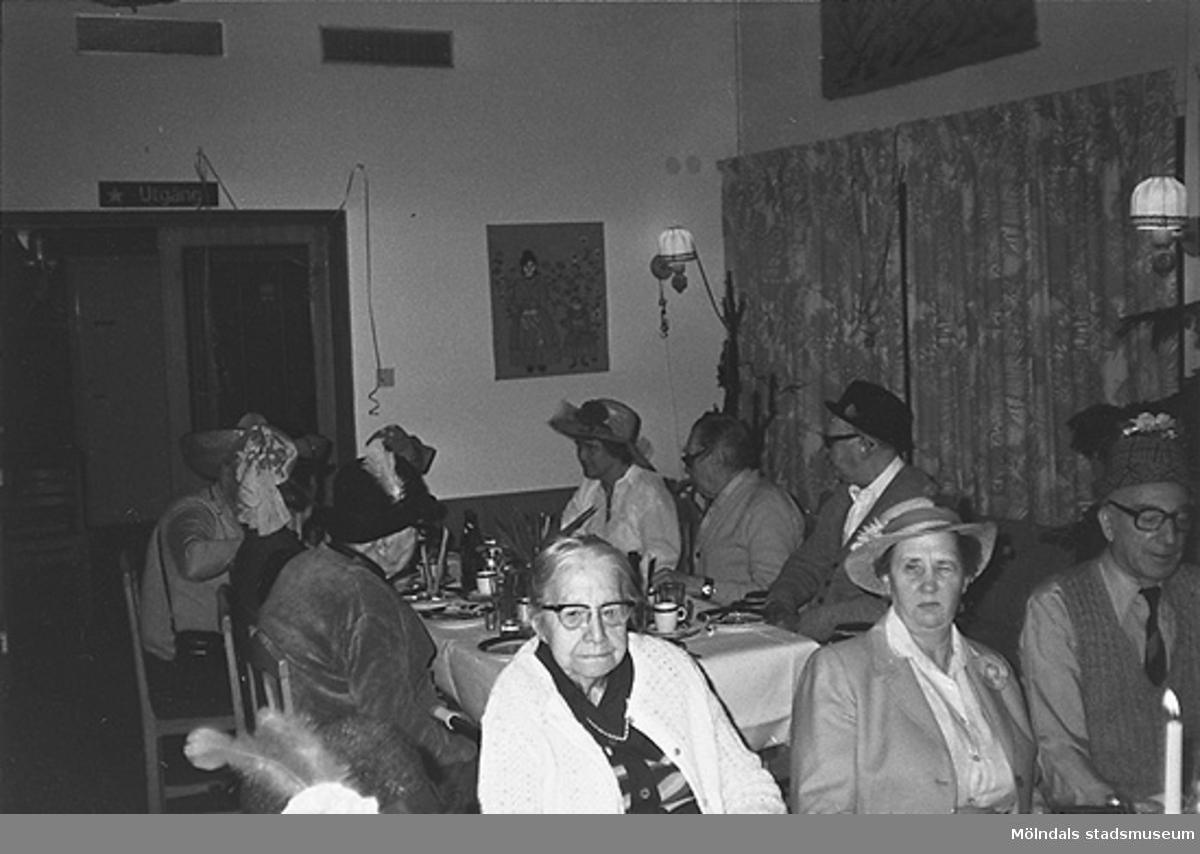 Boende iklädda fina hattar sitter vid bord och fikar. Okänt årtal.