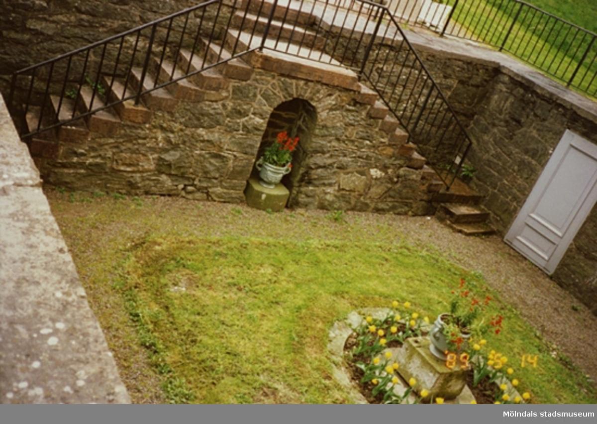 Den nedsänkta innergården (Köksgården) med gräsmatta och blomurna i höger nederkant. Innergården står på Gunnebo slotts östra kortsida (östra parterren). I bakgrunden står en krukväxt placerad i nischen, som är placerad mellan två trappor.
