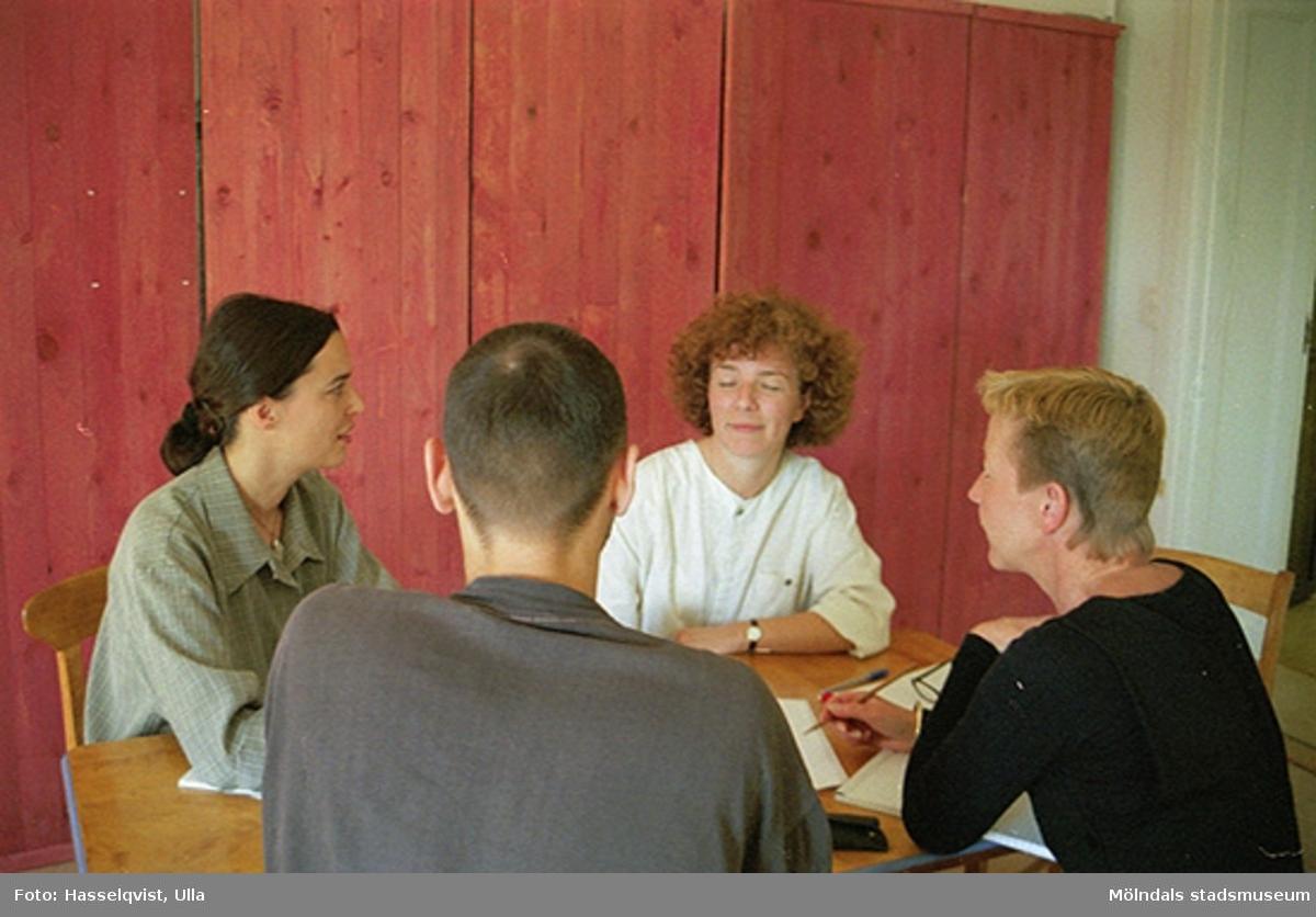 Från vänster: Christina Hill, Ulla Hasselqvist, Håkan Strömberg (frånvänd) och Pia Persson sitter runt ett bord och samtalar.