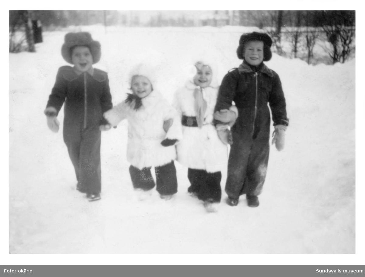 Fyra kusiner på Linneagatan 3 i Skönsberg. Jan Wass från Karlstad, Viveca Söderström i vit getpäls, Margareta Lindqvist i mjuk vit kaninpäls och längst ut till höger Benny Lindqvist. Fotot är taget på Linneagatan 3 i Skönsberg.
