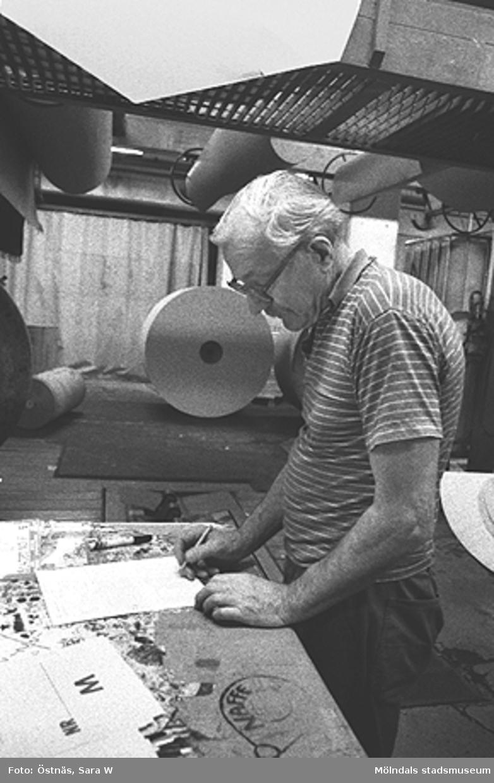 En man i arbete.Bilden ingår i serie från produktion och interiör på pappersindustrin Papyrus.