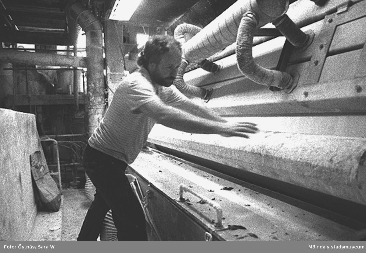 Juris Kuvalds vid en maskin för kartongtillverkning. Bestrykningsverk. Byggnad 6. Bilden ingår i serie från produktion och interiör på pappersindustrin Papyrus.