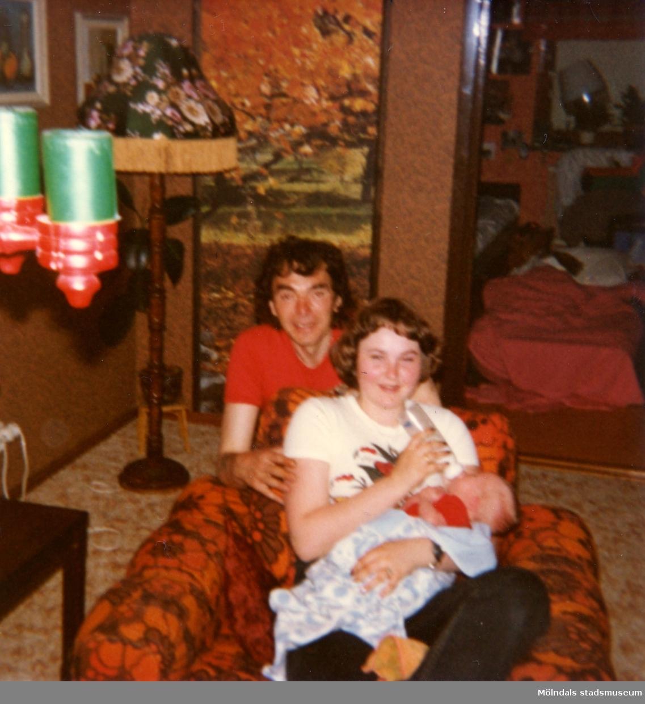 I vardagsrummet hos givarens far Bertil Tobiasson i Ekenässjön utanför Vetlanda, 1977. Givaren, Ilse Jansson, sitter och matar sin lillebror. Mannen bredvid var en vän till familjen.
