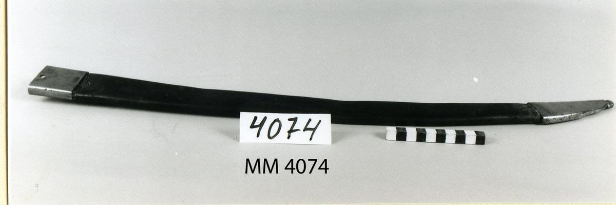 Balja till sabel. Bågformig, av läder. Hylsa av mässing med hake vid fästet och doppsko av mässing.  Baljan tillhör sabel MM 2352.