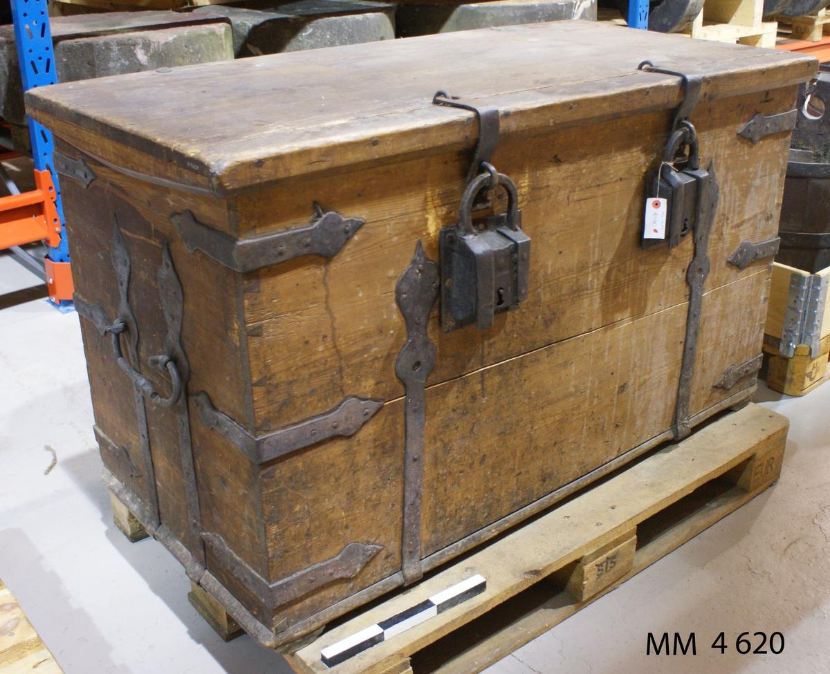 Kista av trä med beslag av smidesjärn. Försedd med två stycken överfall och krampor med två stycken hänglås samt två stycken bärhandtag, allt av smidesjärn.
