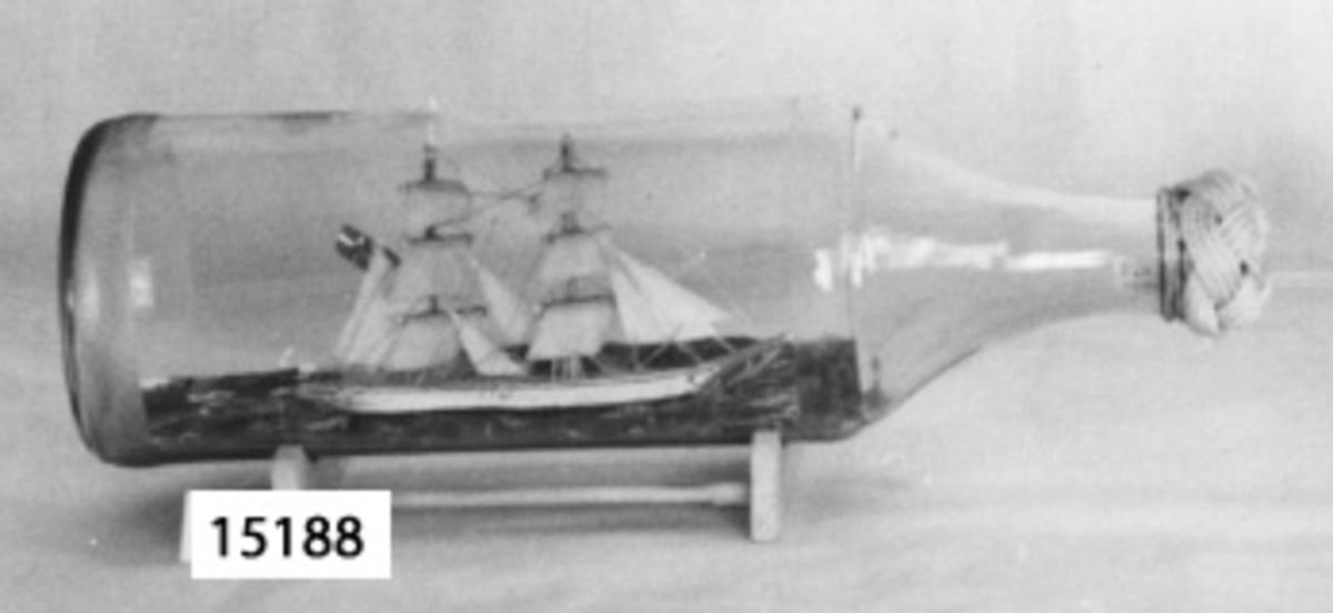 Flaskskepp. Tvåmastat fartyg som bär svensk handelsflagg. Skrovet är vitt med röd botten. Flasskan försluten med en valknop av vitt garn.