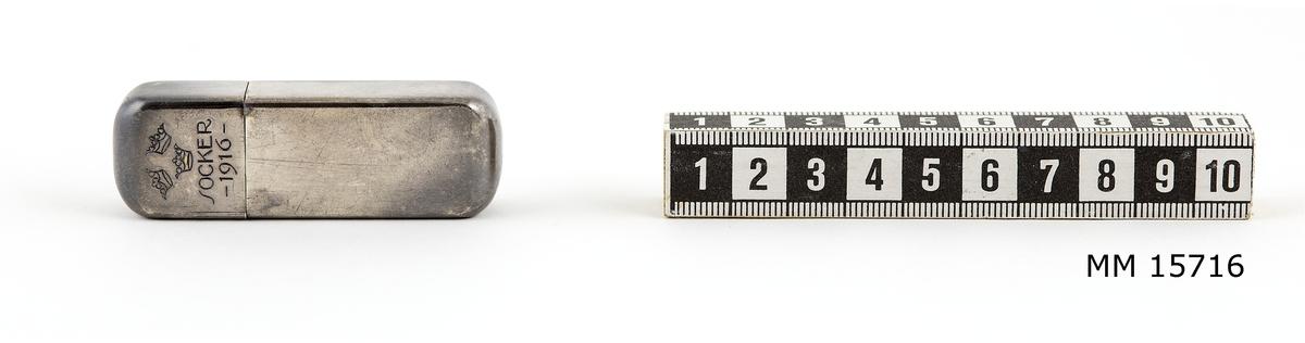 Sockerdosa av nysilver. Rektangulär. På framsidan är tre kronor instämplade, under kronorna SOCKER samt under detta -1916-. På baksidan stämplat: G.A.B. N.S.