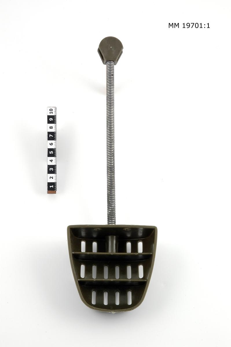 Skoblock bestående av metallfjäder 20 cm lång med en tådel av grön genombruten plast. Fyrkantig tåform är fäst i den ena änden. I den andra en liten rund, platt plastbit som häldel. Märkta i tådelen: Tre Kronor, st 40-43 L.B. Materielnummer: 7335-802000.  Storlek 40-43.