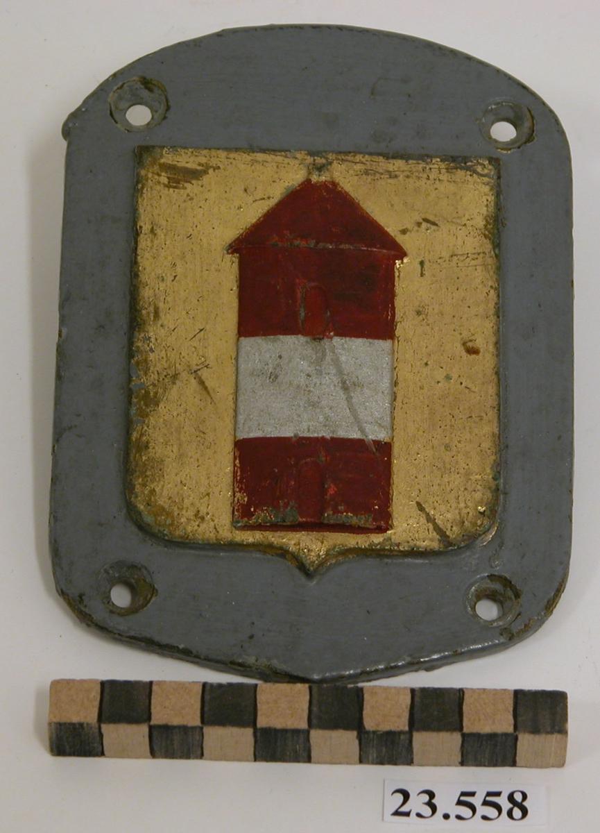 Båtemblem till minsveparen Arholmas livbåtar. Gråmålad platta, i mitten gulbronserad sköld med fyrtornet Arholma i rött med band i silver.