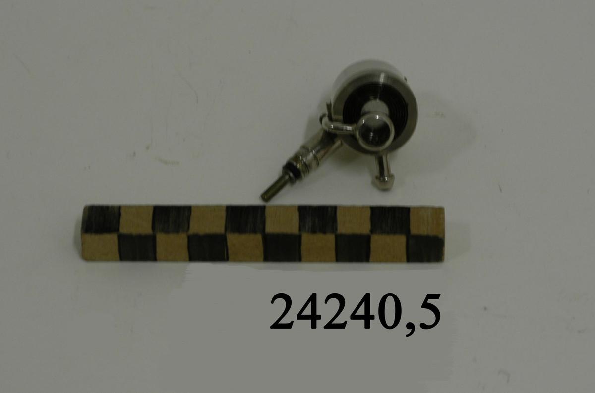 Kort cylinder av rostfritt stål. I dess övre del två stycken linser. Den ena är fäst på en rörlig arm. Den andra är fast. På cylinderns utsida två stycken tappar för anslutning till annan aparatur. I lamphusets insida en liten glödlampa med lins.