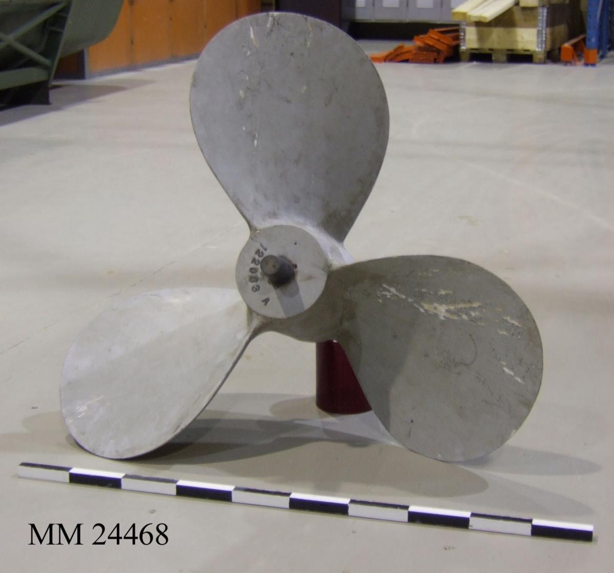 """Gjutformsmodell för 3-bladig propeller. Gråmålad med svarta detaljer. Märkt med en mindre metallplatta, på denna står det: """"122083A""""."""