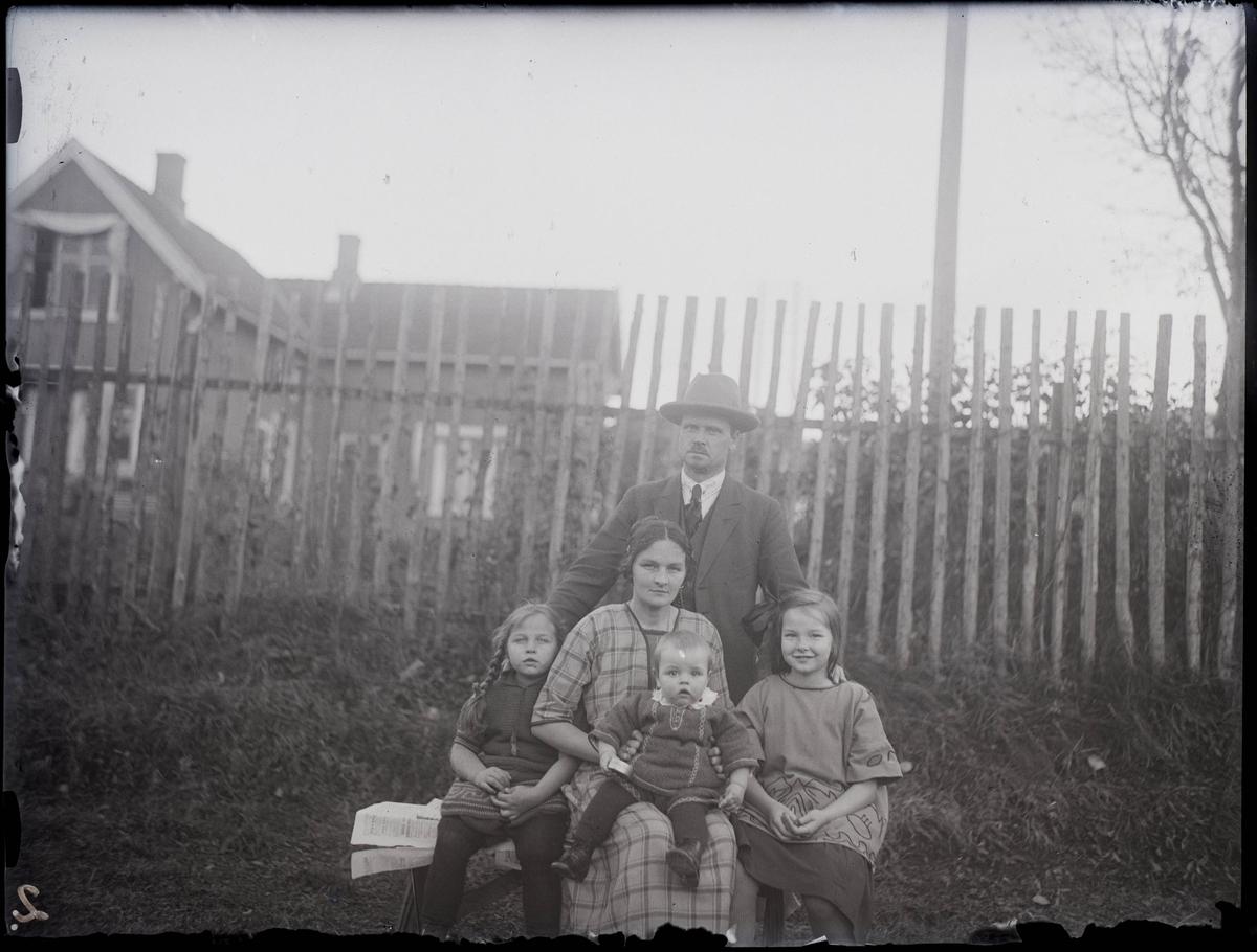 Mann og kone med tre barn utendørs. Familien Berge.