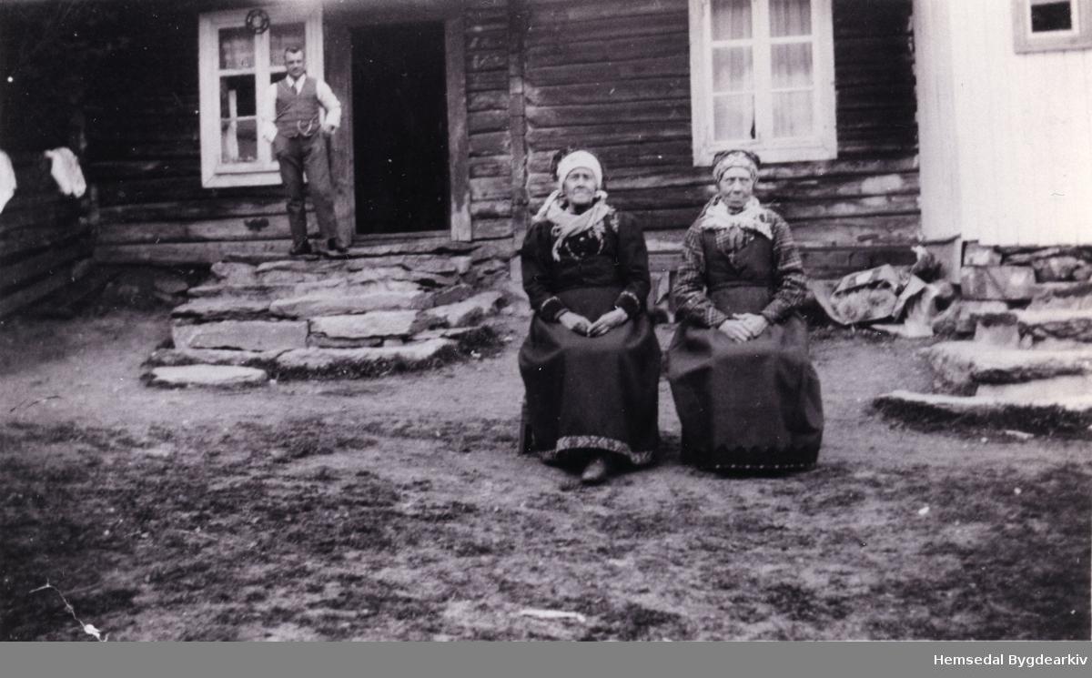 To kjerringar i helgastakk. Frå venstre: Kristi Ødegård, fødd Grøndalen (1845---) Birgit Sletten, fødd Skar (Steinteigen) (1857--) Biletet er teke ca. 1930. Personen på trappa er ikkje identifisert.