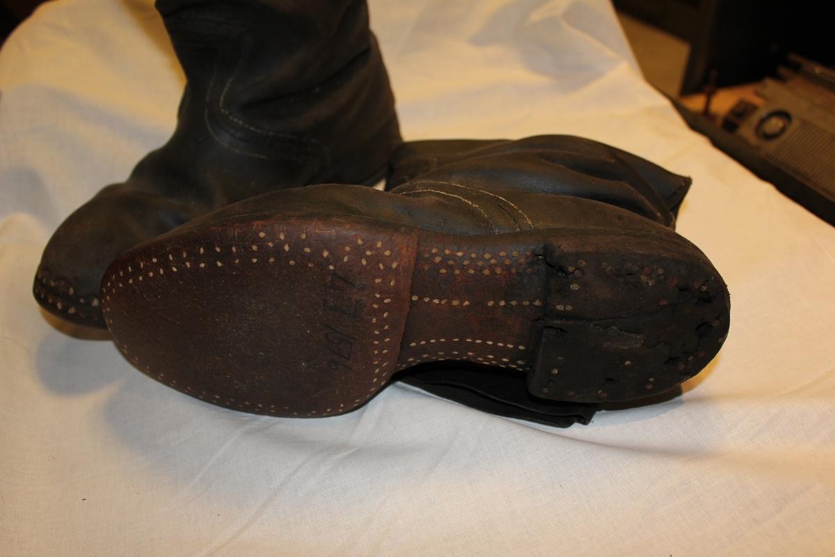 Et par høye lærstøvle. Har en søm foran med hvit tråd. Slitte hæler. Disse støvlene er gamle da resten av sålen er sålt med trenagler / trespiker.