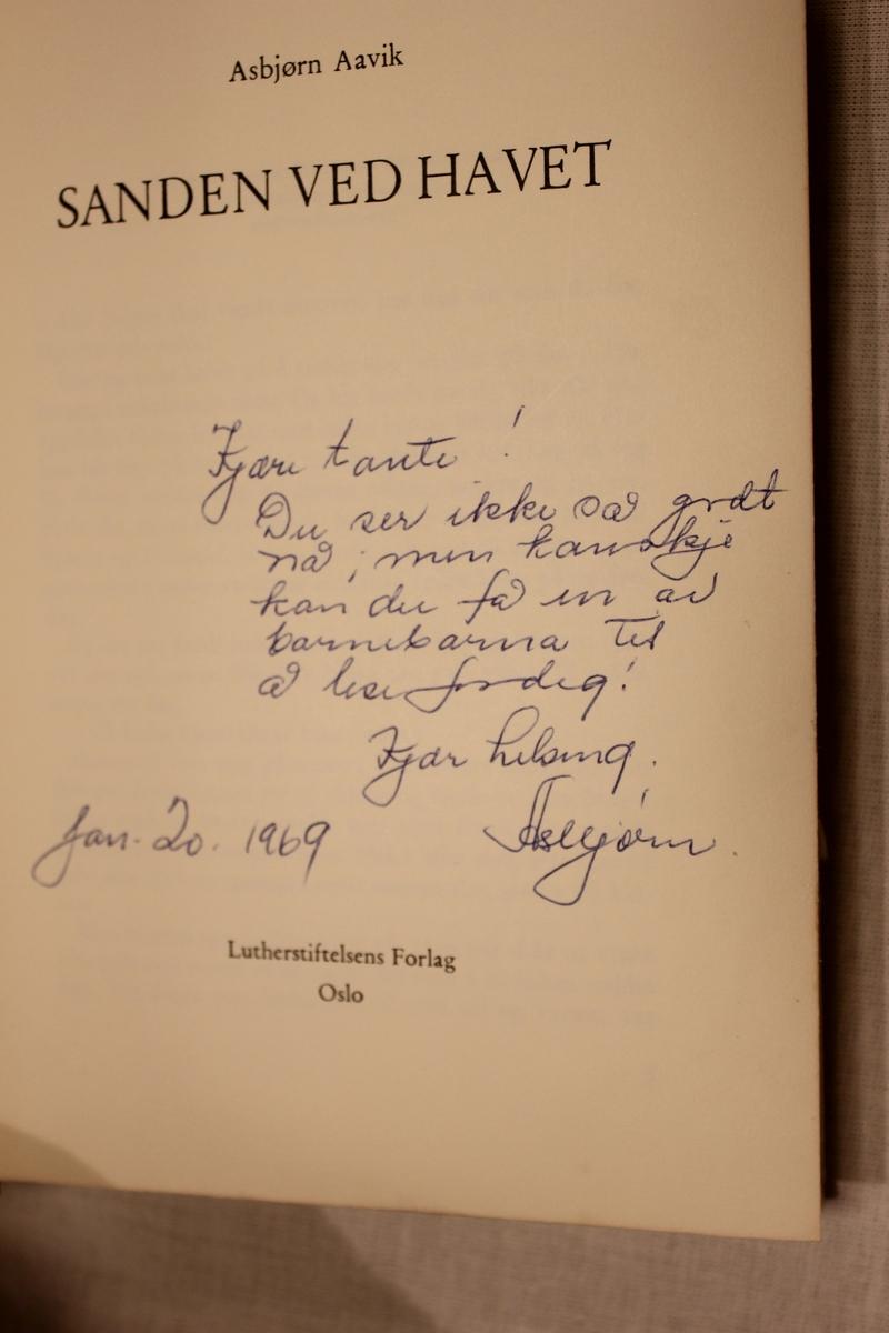 """Tittel """"SANDEN VED HAVET"""" Luther stiftelsens Forlag. Oslo 1968. Omslag: G.B. Bye-Snorre Inskripsjon: """"Kjære Tante. Du ser ikke så godt nå men kanskje kan du få en av barnebarna til å lese for deg. Kjær Helsing. Jan. 20 1969. Asbjørn"""""""