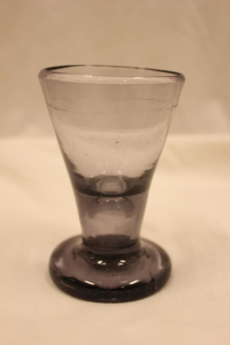 """Ett drikkebeger i glass. Dette er et norsk """"FRIMURER BRENNEVINS GLASS"""" ofte populært kalt """"nøgen(naken) jomfru"""". Pga. fargen er det sansynlighvis fra siste halvdel av 1700- tallet. (Typen glass ble produsert langt opp i 1800- tallet). Glasset ble framstilt ved alle norske glassverk med såkalt """"hvitglass"""" produlsjon, hvor det ble produsert klart glass i motsetning til grønt glass til flasker og vinduer. Glasset var datidens foretrukne brennevinsglass overalt i nordeuropa. De kalles """"frimurerglass"""" i de fleste kataloger og prislister, - dette skyldes at frimurerne hadde en skikk å banke glasset hardt i bordet etter en skål, - dette krevde da en kraftig og solid fot så glasset ikke gikk i stykker. I England kalles de """"firering glass"""" og var ofte brukt i marinen og i militæret. Når alle hadde skålet og drukket, banket de glasset hardt i bordet og det lød som en """"geværsalutt!"""""""