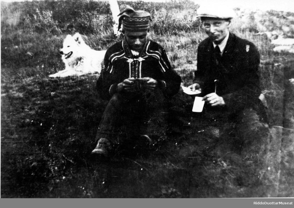 Dievddut cohkkaba olgon, beana goarjada duohken. Menn sitter ute med en hund i bakgrunn.  Issaha-Niillas ja Ante Bongo