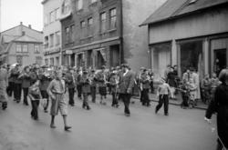 Skolekorps marsjerer ned Strandgata. I forgrunnen et par små