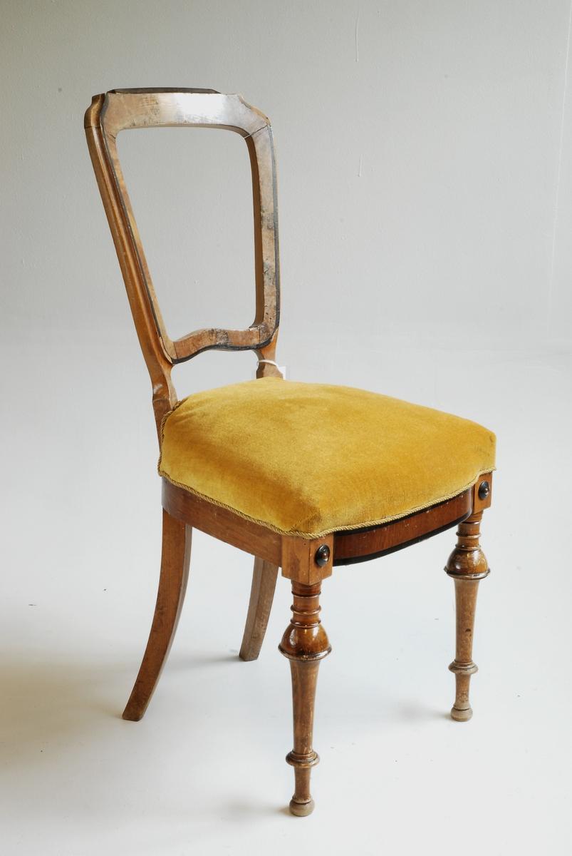 Matstovestol med stoppa sete og ope, rektangulert ryggbrett. Dreia bein i front, med 2 små rosettar mellom sete/stolbein. Dekorelement på øvre del av ryggbrett manglar.