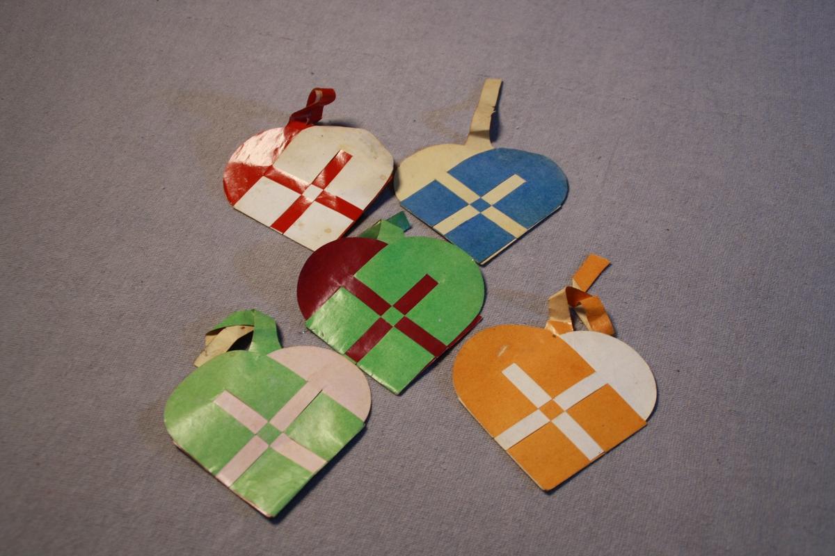Hjerteforma korger fletta av julepapir i to farger. Ulike fargekombinasjoner. Alle flettet i samme mønster - enkelt kryss.