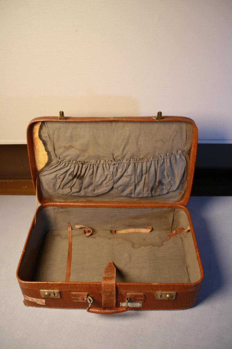 Koffert i skinn.Handtak og to låsar. Skinnreim som går rundt heile kofferten. Innsida er trekt med mønstret stoff, har løsna fleire stadar. Lommer i lokket. Festereimer i skinn.